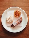 Pretty Italian pastries (including cannoli) on a plate. Three Italian pastries - cannoli, torta della nonna, etc. - on a white plate, shot top down on a wooden Stock Image
