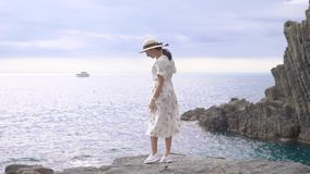 Pretty italian woman is standing on edge of stone coast of sea in daytime, turning to camera and posing. Wearing hat and light dress stock footage