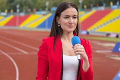 Journalist is reporting from the stadium for TV show Royalty Free Stock Photography