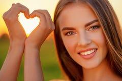 Free Pretty Joyful Girl Gesturing Heart Shaped Over Sunset Backgrou Royalty Free Stock Photo - 130656865