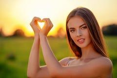 Pretty joyful  girl gesturing heart shaped over sunset background stock image