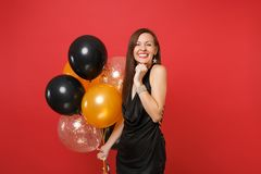 Pretty joyful happy young girl in little black dress celebrating holding air balloons isolated on bright red background royalty free stock photography