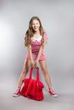 Pretty joyful little girl in a striped dress posing in the studio. Stock Image