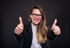 Pretty joyful woman manager with thumbs up. 
