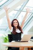 Pretty jubilant clerk. Jubilant female clerk with laptop sitting in office Stock Photography