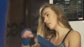 Pretty kickboxing girl training with punching bag in a fitness gym. In full HD stock video footage