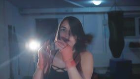 Pretty kickboxing woman training punching bag in sport studio in 4K.  stock video footage