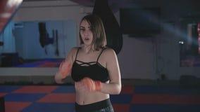 Pretty kickboxing woman training punching bag in sport studio in 4K.  stock video