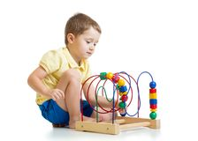 Pretty kid boy plays with color educational toy Stock Photo