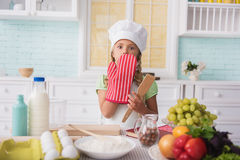 Pretty kid did something wrong in culinary. Oops. Cute little girl made mistake in cooking. She is covering mouth with hand in potholder. Child is standing and Royalty Free Stock Image