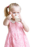 Pretty kid drinking milk from glass. Kid drinking yoghurt from glass and showing thumb up Royalty Free Stock Photos