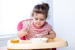 Pretty kid eating with spoon Royalty Free Stock Images