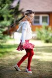 Pretty kid girl dancing outdoors. In a garden Royalty Free Stock Image