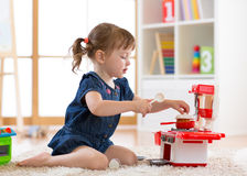 Pretty kid girl playing with a toy kitchen in children room. Or kindergarten royalty free stock photo