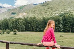 Pretty kid girl resting in mountains. Sitting on the fence, looking back ovet the shoulder, wearing pink clothes stock image