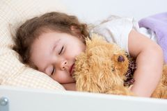 Pretty kid girl sleeping in bed Stock Images