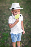 A pretty kid in a hat eating candy on a green background. Cute boy with a lollipop. Kids with sweets. Enjoyment concept. A beautiful small boy with a big candy Royalty Free Stock Photos