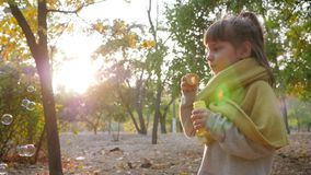 Pretty kid making bubbles on background of sun and trees in autumn park. Pretty kid making bubbles outdoors on background of sun and trees in autumn park stock video footage