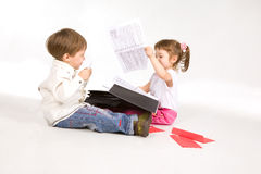 Pretty kids playing with suitcase and papers Stock Images