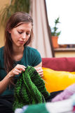 Pretty knitting woman on a couch Stock Photography