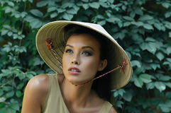 Pretty Korean woman in a three-cornered hat is posing. Pretty Korean woman in a three-cornered hat posing against a background of wild grapes Royalty Free Stock Images