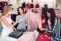 Pretty ladies are in store. They are holding one pink sport sweatshirt. Asian girl is looking at blonde one and smiling. While brunette girl is looking at stock photography