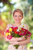 Pretty lady with armful of wildflowers Stock Photography