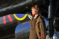 Pretty lady in army uniform with WWII bomber Royalty Free Stock Images