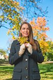 Pretty Lady in Autumn Fashion Holding Dry Leaves Stock Photo