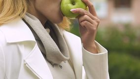 Pretty lady biting fresh green apple healthy snacks during lunch time, nutrition. Stock footage stock video footage