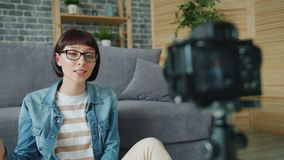 Pretty lady blogger recording video at home using professional camera on tirpod. Talking gesturing showing v-sign gesture. Blogging and millennials concept stock video footage