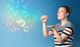 Pretty lady blowing colorful bubbles on blue background Stock Image
