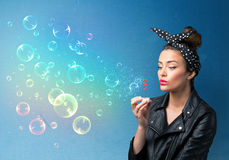 Pretty lady blowing colorful bubbles on blue background Stock Photography