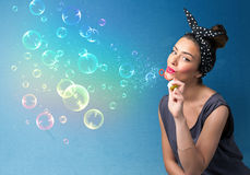 Pretty lady blowing colorful bubbles on blue background Stock Photo