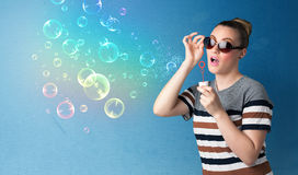 Pretty lady blowing colorful bubbles on blue background Royalty Free Stock Photos