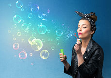 Pretty lady blowing colorful bubbles on blue background Royalty Free Stock Image
