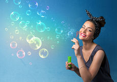 Pretty lady blowing colorful bubbles on blue background Stock Photos