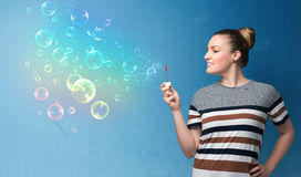 Pretty lady blowing colorful bubbles on blue background Royalty Free Stock Photography
