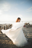 Pretty lady, bride posing in a wedding dress near sea on sunset.  Royalty Free Stock Photography
