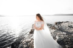Pretty lady, bride posing in a wedding dress near sea on sunset Stock Photo