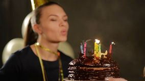 Pretty Lady in Cap is Blowing out Her Birthday Candles on Chocolate Cake and Applauding. Woman with Charming Smile on