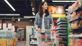 Pretty lady in casual clothes is walking in grocery store steering shopping trolley with food inside it and looking