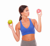 Pretty lady choosing between fruit and donut Stock Photos