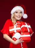 Pretty lady in Christmas cap holds presents Royalty Free Stock Images