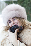 Pretty lady cuddle her little dog in winter time Stock Image