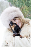 Pretty lady cuddle her little dog in winter time. After a big snowfall Stock Photos