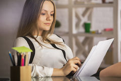 Pretty lady doing paperwork. Close up portrait of pretty young caucasian lady doing paperwork at desk with laptop, supplies and other items Stock Photos