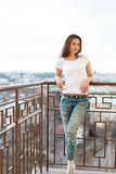 Pretty lady enjoying the weather and a photosession having place on the balcony of her hotel. Royalty Free Stock Photo