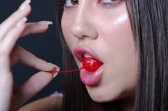 Pretty lady with fleshy lips, biting a sweet cherry. Pretty lady model with pink tone makeup, brown almond eyes, fleshy lips, holding with her long slim fingers royalty free stock photography