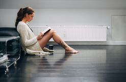 Pretty lady on floor at home reading a novel Stock Images